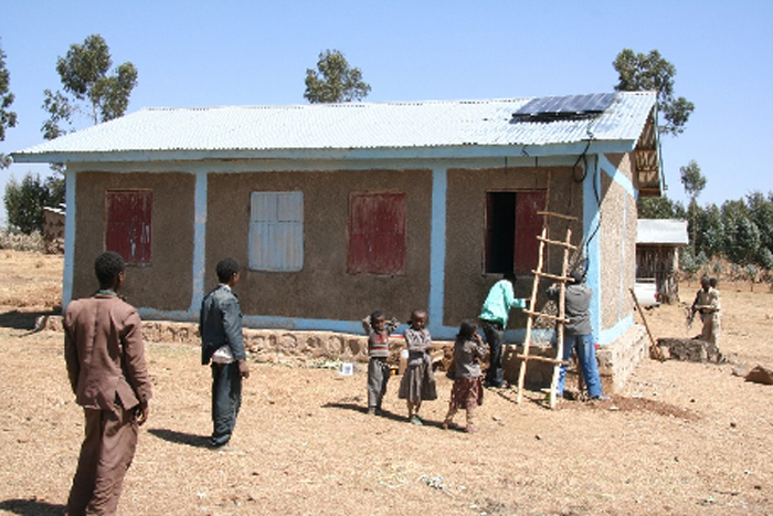 Rural Health post at Beso being fitted with a solar panel to run a vaccine fridge